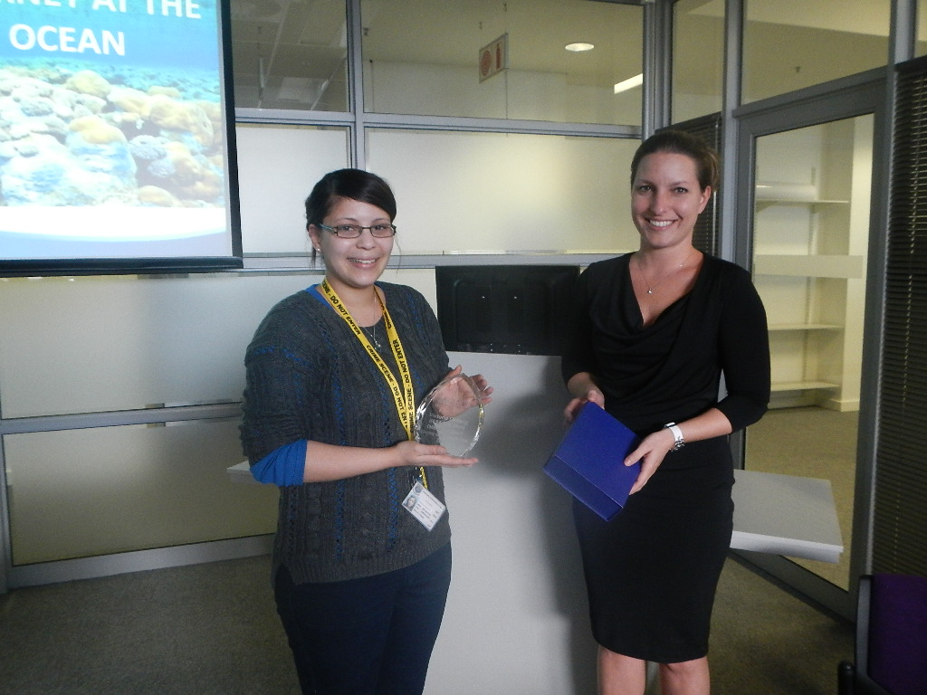 Victoria Ontong receives the prize from Roche representative Tamara Fedderke